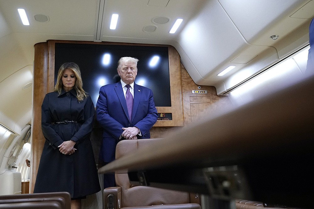 President Donald Trump and first lady Melania Trump pause for a moment of silence on Air Force One as he arrives at the airport in Johnstown, Pa., on his way to speak at the Flight 93 National Memorial, Friday, Sept. 11, 2020, in Shanksville, Pa. (AP Photo/Alex Brandon)