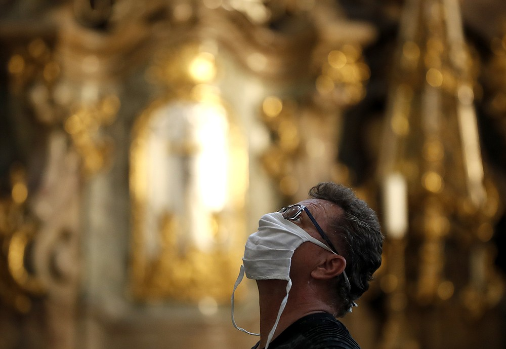 A man wearing a face mask visit the St. Nicholas church in Prague, Czech Republic, Thursday, Sept. 10, 2020. The Czech Republic is returning to mandatory mask wearing in interior spaces amid a steep rise in new coronavirus cases. Starting Thursday, people across the country need to cover their face in all public places, including stores, shopping malls, post offices and others but also in private companies where employees cannot keep a distance of 2 meters from one another. (AP Photo/Petr David Josek)