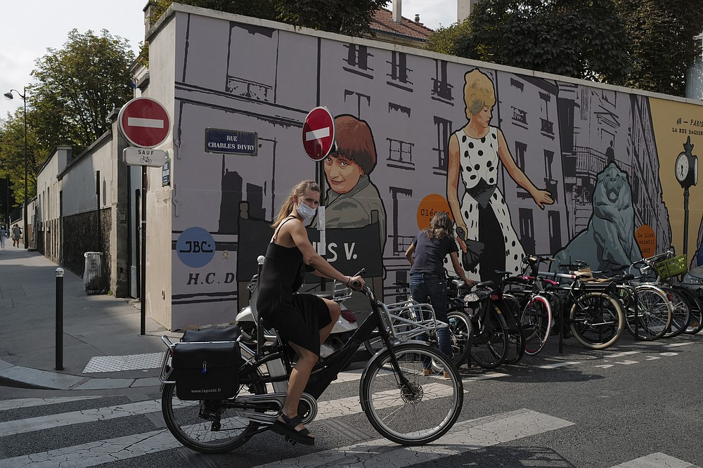 A woman, wearing a protective face mask as a precaution against the coronavirus, rides her bicycle front of a mural representing late film director Agnes Varda, in Paris, Friday, Sept. 11, 2020. French health authorities have reported on Thursday 9,843 infections from the coronavirus in 24 hours, the highest daily tally since the end of France's lockdown in April. France has seen a sharp uptick in new cases in recent weeks and hospitalizations have started to increase steadily, reaching now over 5,000 including 615 people in ICU. (AP Photo/Francois Mori)