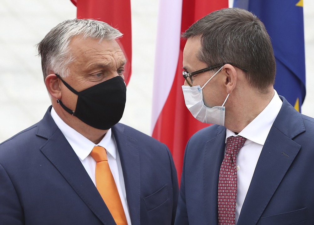 Poland's Prime Minister Mateusz Morawiecki, right, is greeting his counterpart from Hungary, Viktor Orban, left, at the start of the Visegrad Group premiers' meeting in Lublin, Poland, Friday, Sept. 11, 2020. In preparation for European Union summit this month, the meeting is to discuss situation in Belarus, ties with Russia and fighting COVID-19. (AP Photo/Czarek Sokolowski)
