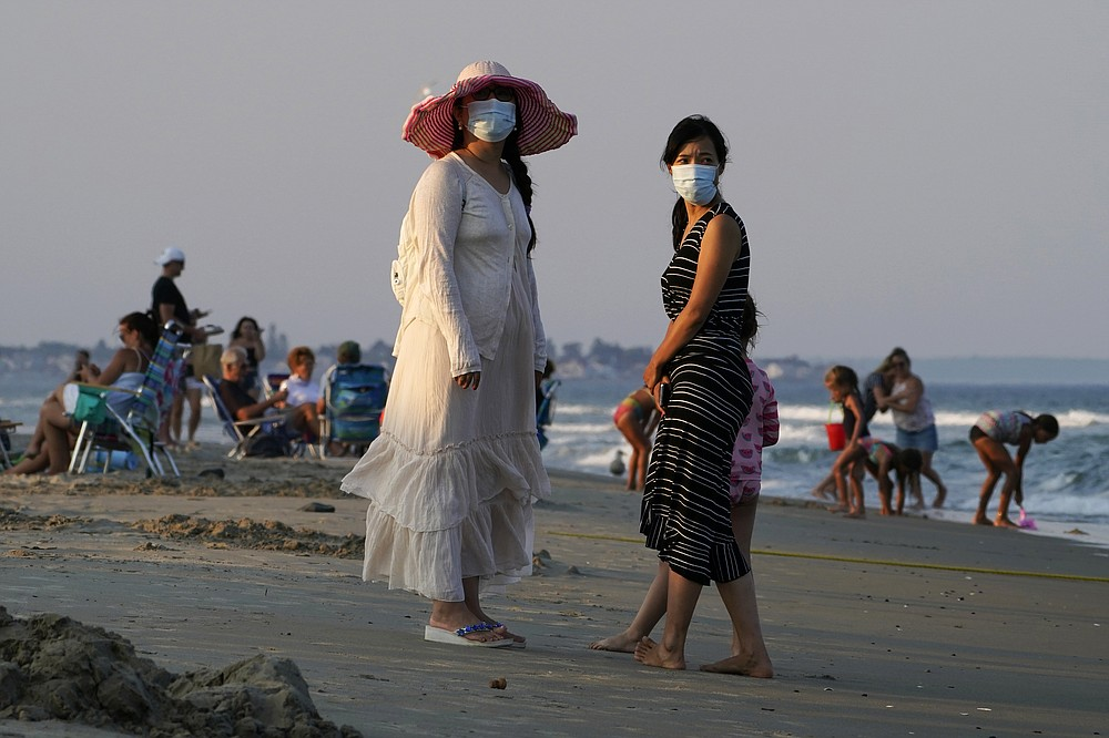 FILE - In this Aug. 11, 2020, file photo, women wear masks to help prevent the spread of coronavirus at the end of a beach day in Ogunquit, Maine. The number of daily U.S. deaths from the coronavirus is declining again after peaking in early August, but scientists are warning that a new bout with the disease this fall could claim more lives. Experts say the arrival of cooler weather and the likelihood of more indoor gatherings will add to the importance of everyday safety precautions, like wearing masks, staying home and washing hands. (AP Photo/Robert F. Bukaty, File)