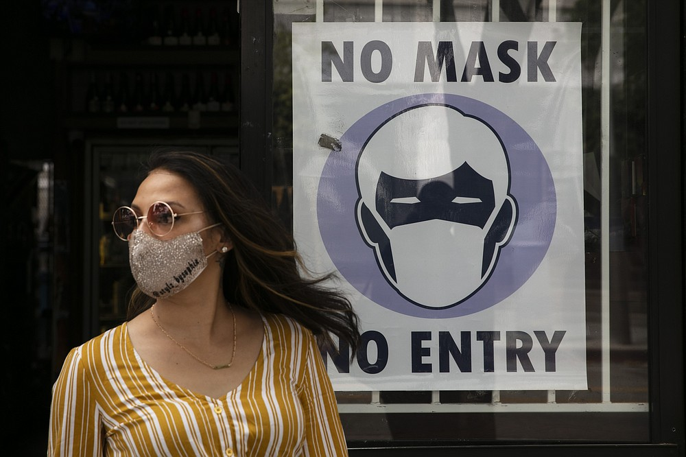 FILE - In this June 23, 2020, file photo, a woman walks out of a liquor store past a sign requesting its customers to wear a mask in Santa Monica, Calif. The number of daily U.S. deaths from the coronavirus is declining again after peaking in early August, but scientists are warning that a new bout with the disease this fall could claim more lives. Experts say the arrival of cooler weather and the likelihood of more indoor gatherings will add to the importance of everyday safety precautions, like wearing masks, staying home and washing hands. (AP Photo/Jae C. Hong, File)