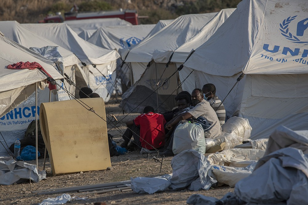 Migrants sit next to the tents at a temporary camp near Mytilene town, on the northeastern island of Lesbos, Greece, Saturday, Sept. 12, 2020. Greek authorities have been scrambling to find a way to house more than 12,000 people left in need of emergency shelter on the island after the fires deliberately set on Tuesday and Wednesday night gutted the Moria refugee camp. (AP Photo/Petros Giannakouris)