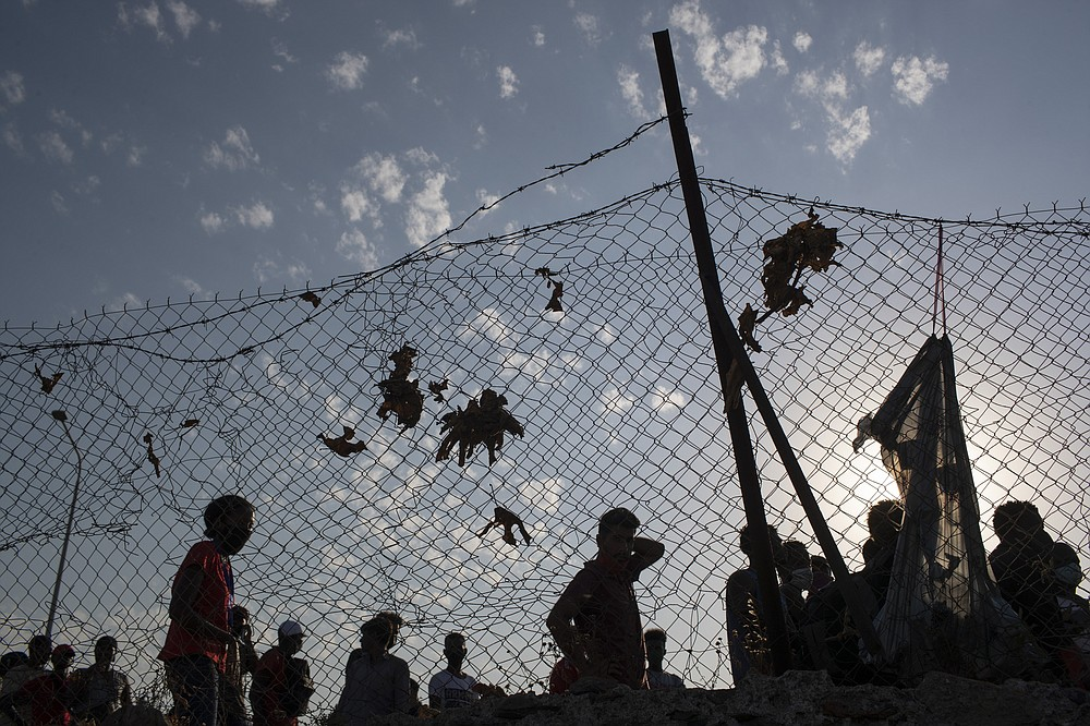 Migrants arrive a temporary camp near Mytilene town, on the northeastern island of Lesbos, Greece, Saturday, Sept. 12, 2020. Greek authorities have been scrambling to find a way to house more than 12,000 people left in need of emergency shelter on the island after the fires deliberately set on Tuesday and Wednesday night gutted the Moria refugee camp. (AP Photo/Petros Giannakouris)