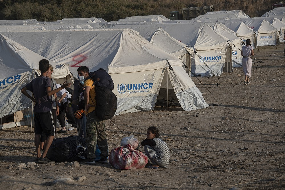 Migrants arrive at a temporary camp near Mytilene town, on the northeastern island of Lesbos, Greece, Saturday, Sept. 12, 2020. Greek authorities have been scrambling to find a way to house more than 12,000 people left in need of emergency shelter on the island after the fires deliberately set on Tuesday and Wednesday night gutted the Moria refugee camp. (AP Photo/Petros Giannakouris)