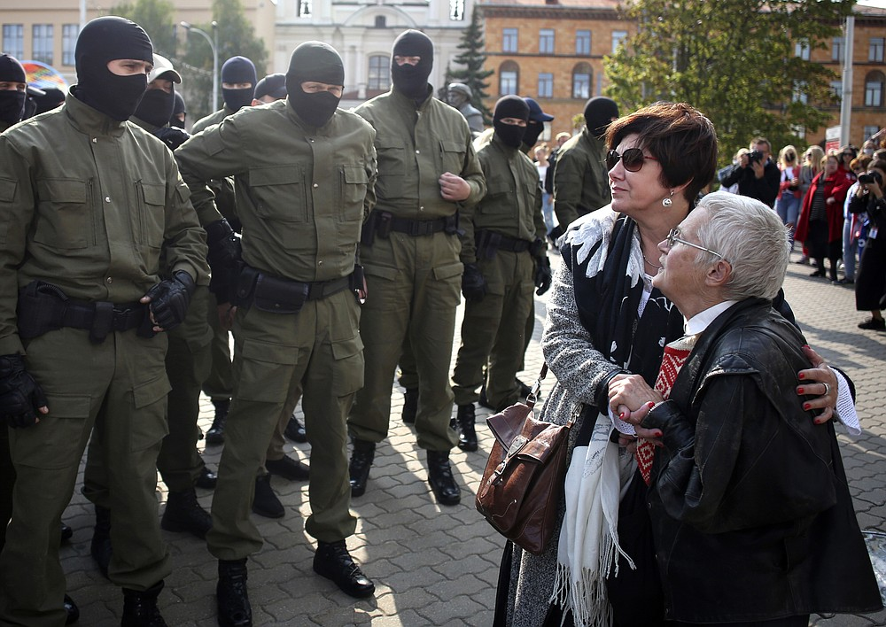 Women react, standing in front of police line during an opposition rally to protest the official presidential election results in Minsk, Belarus, Saturday, Sept. 12, 2020. Daily protests calling for the authoritarian president's resignation are now in their second month and opposition determination appears strong despite the detention of protest leaders. (Tut.by via AP)