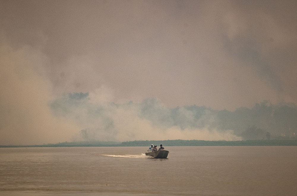 A boat travels at the Encontro das Aguas park as fire consumes an area at the Pantanal wetlands near Pocone, Mato Grosso state, Brazil, Saturday, Sept. 12, 2020. Wildfire has infiltrated the state park, an eco-tourism destination known for its population of jaguars. (AP Photo/Andre Penner)