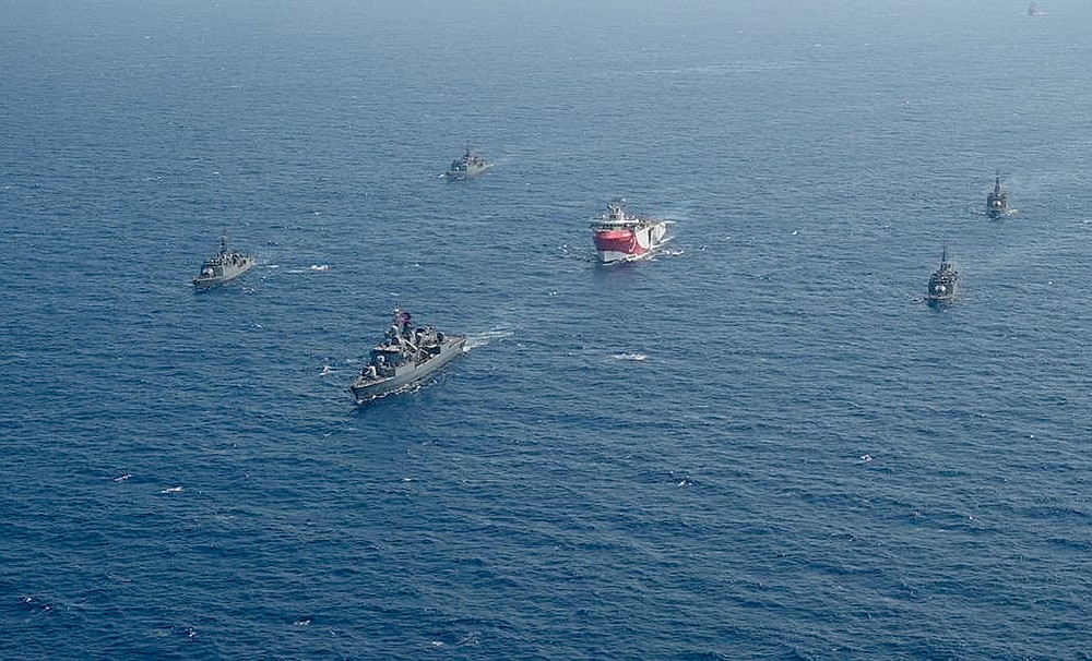 FILE - In this photo taken Monday, Aug. 10, 2020, Turkey's research vessel, Oruc Reis, center, is surrounded by Turkish navy vessels as it was heading in the west of Antalya on the Mediterranean, Turkey. Greece says it will conduct a navy and air force exercise in an area of the eastern Mediterranean where Turkey is prospecting for oil and gas in an area as the neighboring countries remain locked in a dispute over offshore energy rights. (IHA via AP)