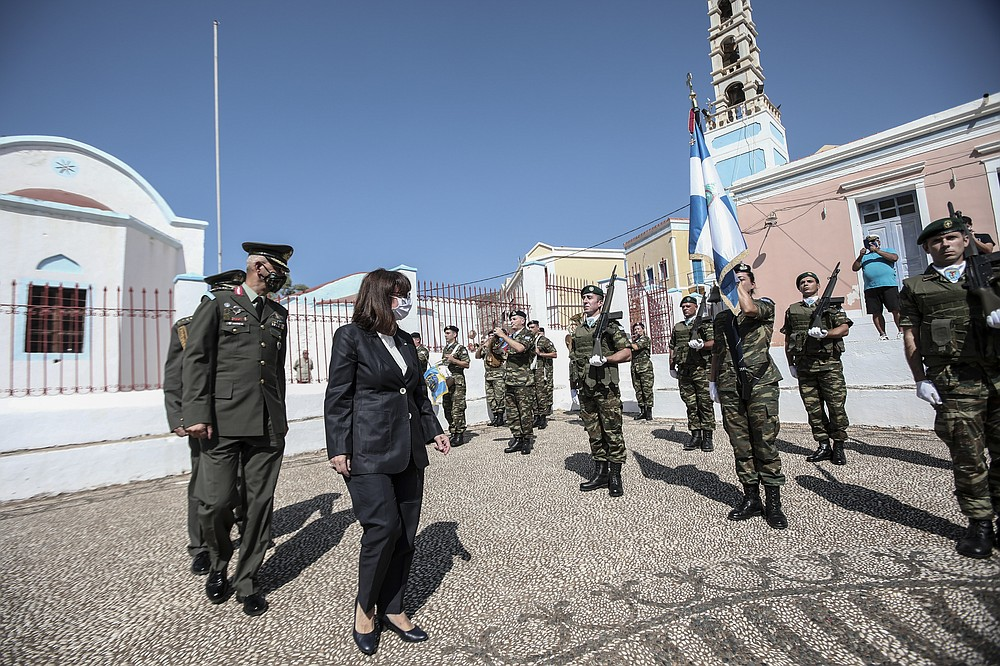 In this photo provided by the Greek President's office on Sunday, Sept. 13, 2020, Greece's President Katerina Sakellaropoulou inspects a guard of honour during celebrations marking when the southeastern island of Kastellorizo, formally became part of Greece. Greece's prime minister outlined plans Saturday to upgrade the country's defense capabilities, including purchasing new fighter planes, frigates, helicopters and weapons systems amid heightened tensions with Turkey over rights to resources in the eastern Mediterranean. (Thodoris Manolopoulos/Greek President's Office via AP)