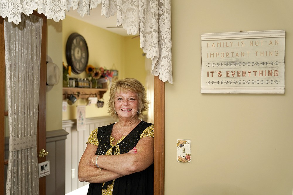 """Kay Orzechowicz poses Wednesday, Sept. 2, 2020, for a portrait at her Griffith, Ind., home. After 35 years of teaching, Orzechowicz said COVID-19 """"pushed her over the edge"""" to retire from northwest Indiana's Griffith High School at the end of July. Turning 58 in October, Orzechowicz had hoped to keep teaching for a few more years before retiring from the classroom. But after the pandemic intensified in March, the English teacher said her concerns about holding out mounted. (AP Photo/Charles Rex Arbogast)"""