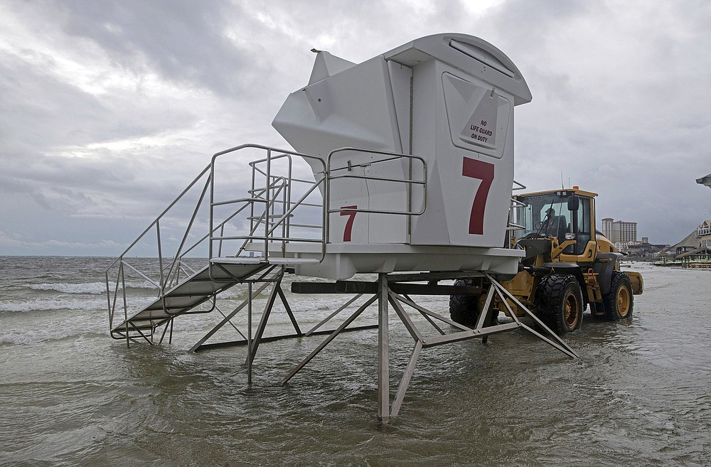 A lifeguard stand is removed from a flooded beach in Pensacola Beach, Monday, Sept. 14, 2020. Storm-weary Gulf Coast residents rushed to finish last-minute preparations Monday as Hurricane Sally chugged slowly through warm Gulf waters. Forecasters predicted the biggest threat is flooding, with as much as two feet of rain falling in some areas. (Tony Giberson/Pensacola News Journal via AP)