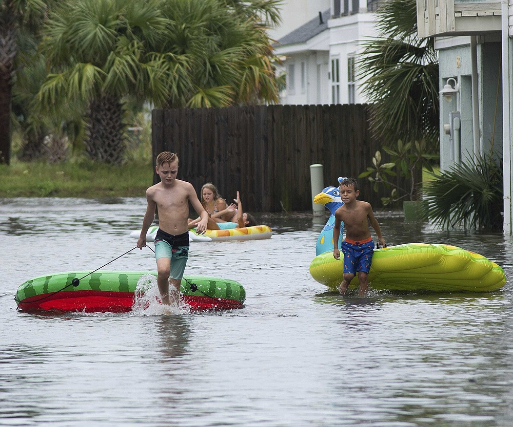 Landon Suarez and Landon Campbell turn the flooded parking lot of the Bahia-Paz condos into a waterpark, Monday, Sept. 14, 2020, in Pensacola Beach, Fla. Storm-weary Gulf Coast residents rushed to finish last-minute preparations Monday as Hurricane Sally chugged slowly through warm Gulf waters. Forecasters predicted the biggest threat is flooding, with as much as two feet of rain falling in some areas. (Tony Giberson/Pensacola News Journal via AP)