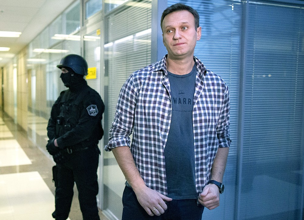 FILE- In this Dec. 26, 2019, file photo, Russian opposition leader Alexei Navalny speaks to the media in front of a security officer standing guard at the Foundation for Fighting Corruption office in Moscow, Russia. The German government says specialist labs in France and Sweden have confirmed Russian opposition leader Alexei Navalny was poisoned with the Soviet-era nerve agent Novichok. (AP Photo/Alexander Zemlianichenko, File)