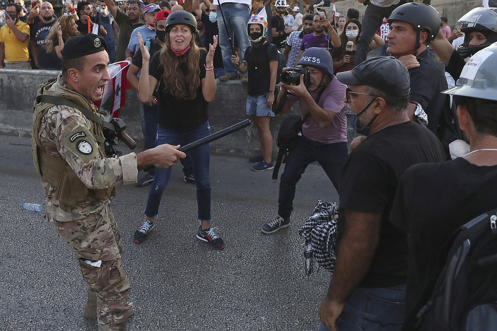 A Lebanese army soldier shouts as he tries to push back the anti-government protesters, during a protest against the Lebanese President Michel Aoun near the presidential palace, in Baabda east of Beirut, Lebanon, Saturday, Sept. 12, 2020. Soldiers fired rubber bullets and live rounds in the air to disperse hundreds of protesters trying to march to the presidential palace during an anti-government demonstration. (AP Photo/Bilal Hussein)