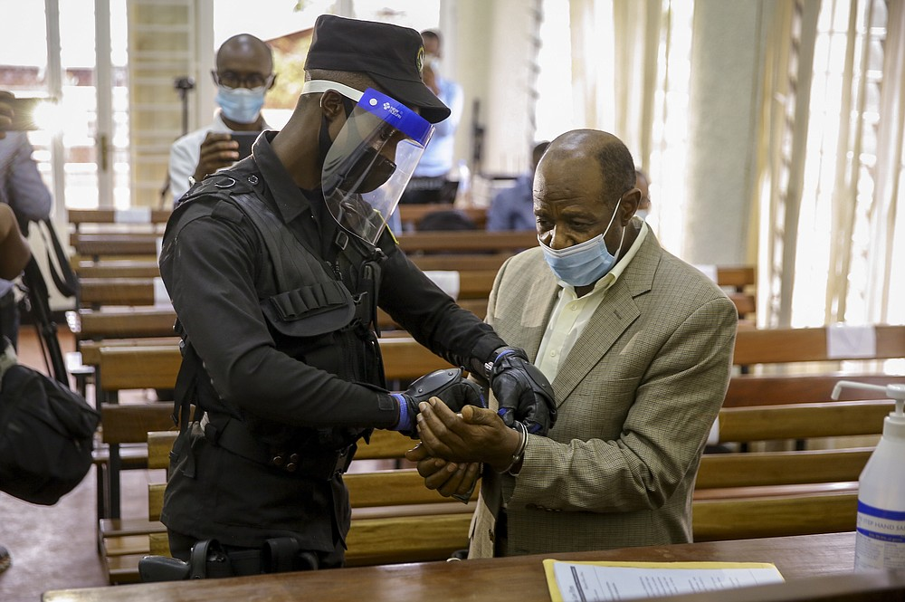 "A policeman handcuffs Paul Rusesabagina, right, whose story inspired the film ""Hotel Rwanda"", before leading him out of the Kicukiro Primary Court in the capital Kigali, Rwanda Monday, Sept. 14, 2020. A Rwandan court on Monday charged Paul Rusesabagina with terrorism, complicity in murder, and forming an armed rebel group, while Rusesabagina declined to respond to all 13 charges, saying some did not qualify as criminal offenses and saying that he denied the accusations when he was questioned by Rwandan investigators. (AP Photo/Muhizi Olivier)"
