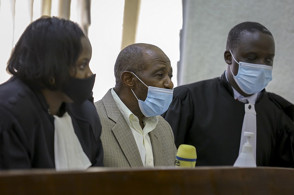 "Paul Rusesabagina, center, whose story inspired the film ""Hotel Rwanda"", appears at the Kicukiro Primary Court in the capital Kigali, Rwanda Monday, Sept. 14, 2020. A Rwandan court on Monday charged Paul Rusesabagina with terrorism, complicity in murder, and forming an armed rebel group, while Rusesabagina declined to respond to all 13 charges, saying some did not qualify as criminal offenses and saying that he denied the accusations when he was questioned by Rwandan investigators. (AP Photo/Muhizi Olivier)"