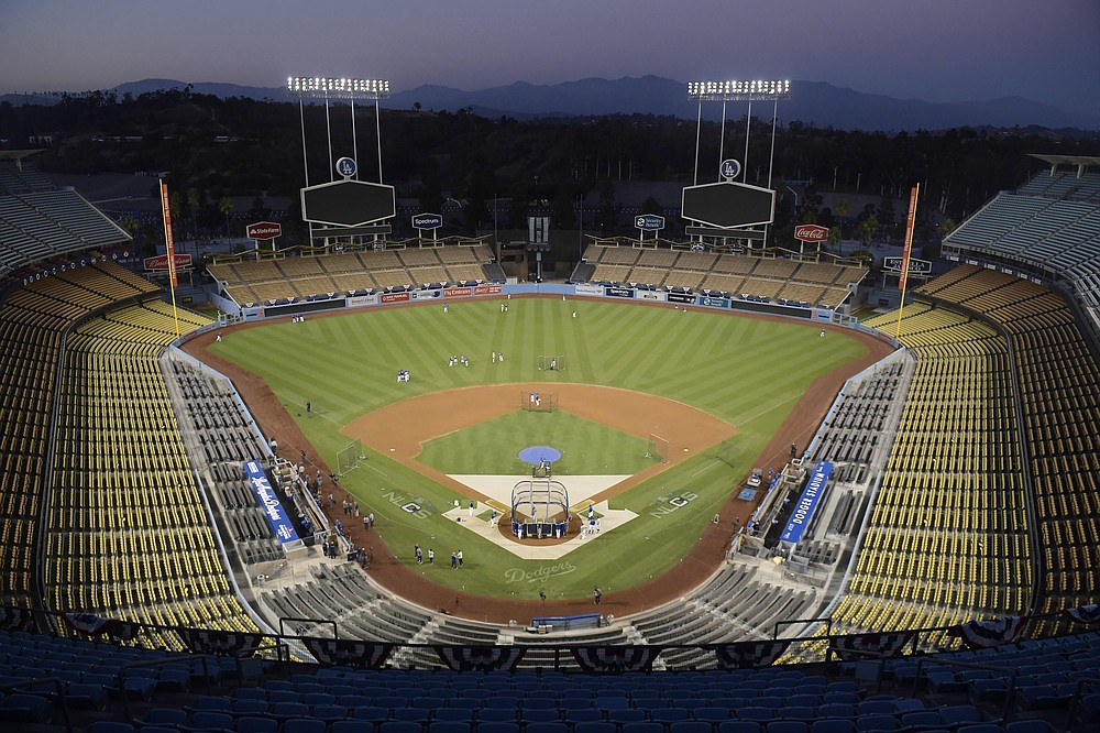 FILE - In Oct. 10, 2018, file photo, Dodger Stadium is shown after sunset in Los Angeles. The Division Series, League Championship Series and World Series will be part of a bubble designed to minimize exposure to the coronavirus. The AL Division Series will be at San Diego's Petco Park and Los Angeles' Dodger Stadium, and the NL Division Series at Arlington's Globe Life and Houston's Minute Maid Park. (AP Photo/Mark J. Terrill, File)