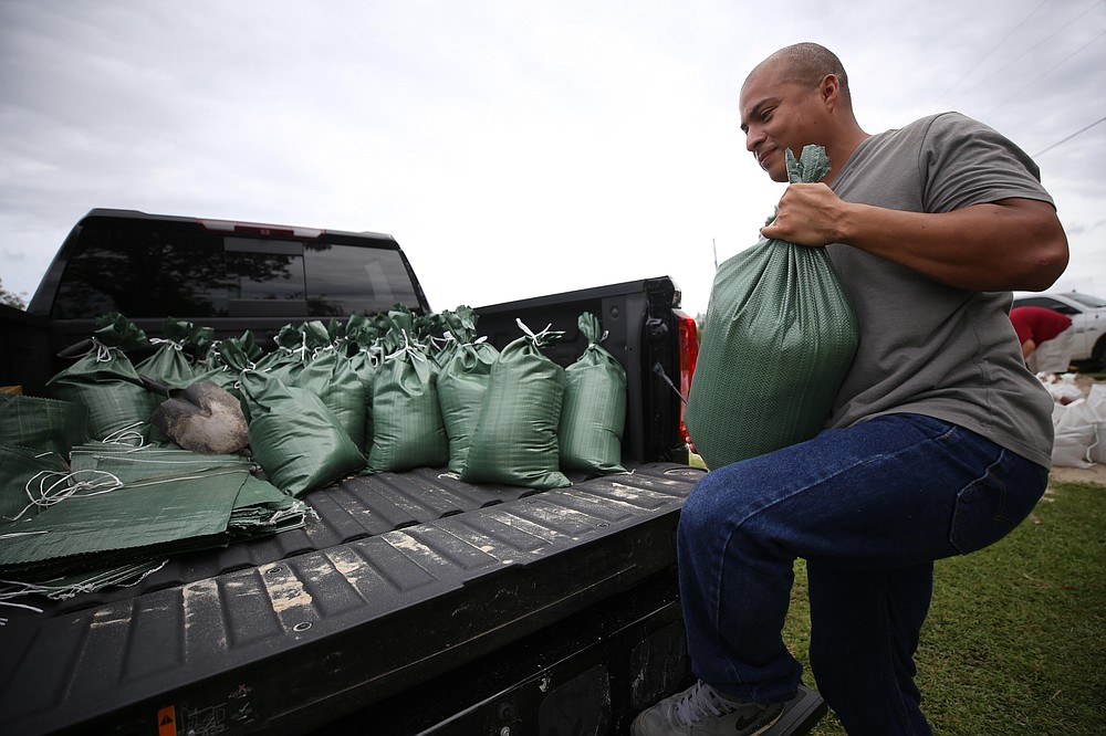 Fabian Barreto loads sandbags into his pickup truck, Monday, Sept. 14, 2020, in Gulfport, Miss. Barreto and his wife, Desi Barreto, live in a new home subdivision in Gulfport and their backyard easily floods. They hope the bags will keep water from flooding the house. (Alyssa Newton/The Sun Herald via AP)