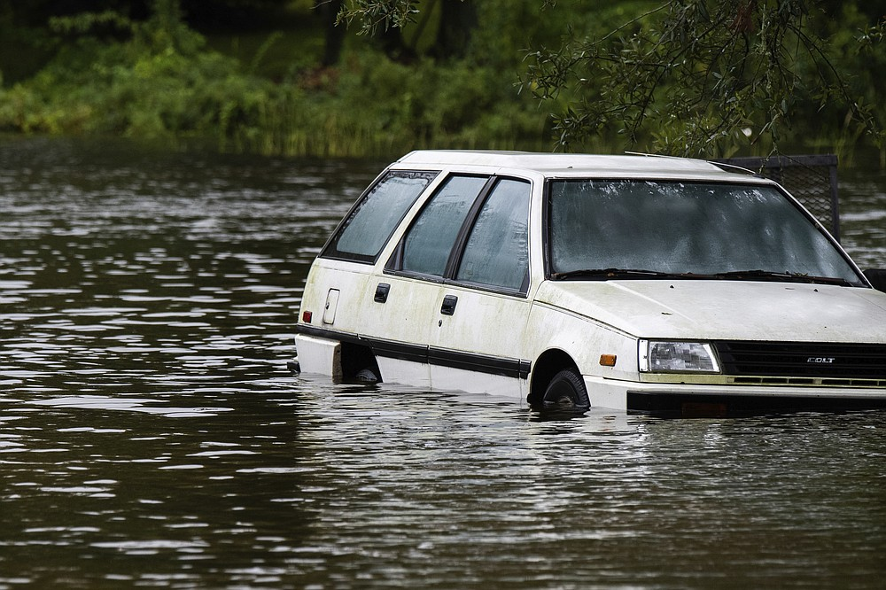 An empty vehicle sits in floodwaters in a driveway in Pascagoula, Miss., Tuesday, Sept. 15, 2020. The low-lying neighborhood was overtaken by flooding from rains associated with Hurricane Sally. (Lukas Flippo/The Sun Herald via AP)
