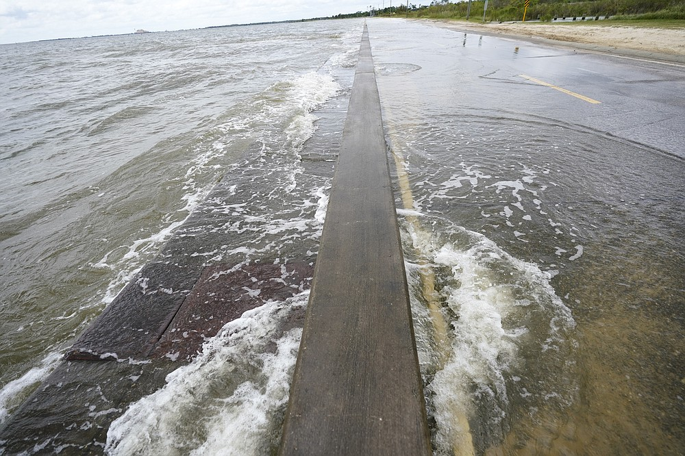 Waters from the Gulf of Mexico poor onto a local road, Monday, Sept. 14, 2020, in Waveland, Miss. Hurricane Sally, one of a record-tying five storms churning simultaneously in the Atlantic, closed in on the Gulf Coast on Monday with rapidly strengthening winds of at least 100 mph (161 kph) and the potential for up to 2 feet (0.6 meters) of rain that could bring severe flooding. (AP Photo/Gerald Herbrt)