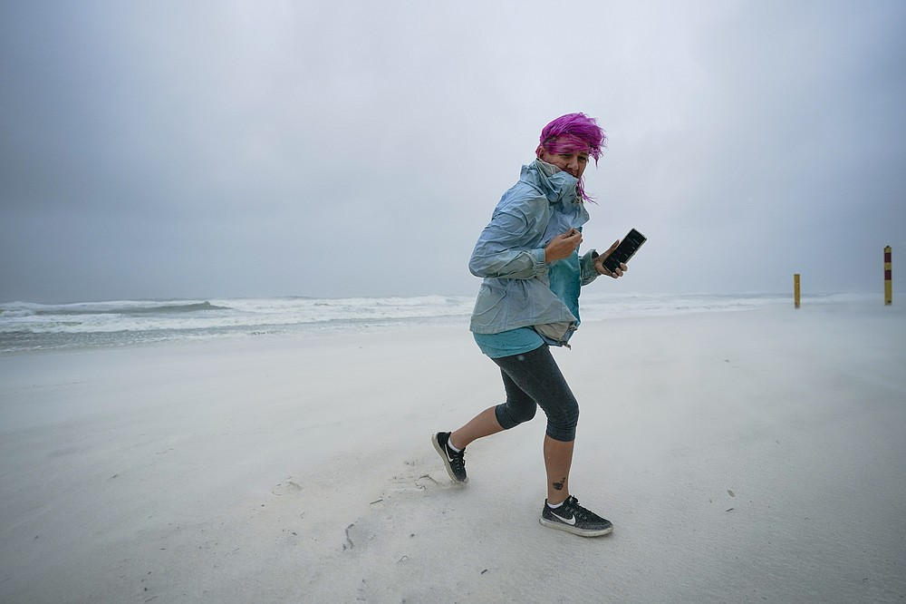Courtney Watts, of Tuscaloosa, Ala., moves off the beach at Gulf State Park, Tuesday, Sept. 15, 2020, in Gulf Shores, Ala. Hurricane Sally is crawling toward the northern Gulf Coast at just 2 mph, a pace that's enabling the storm to gather huge amounts of water to eventually dump on land. (AP Photo/Gerald Herbrt)