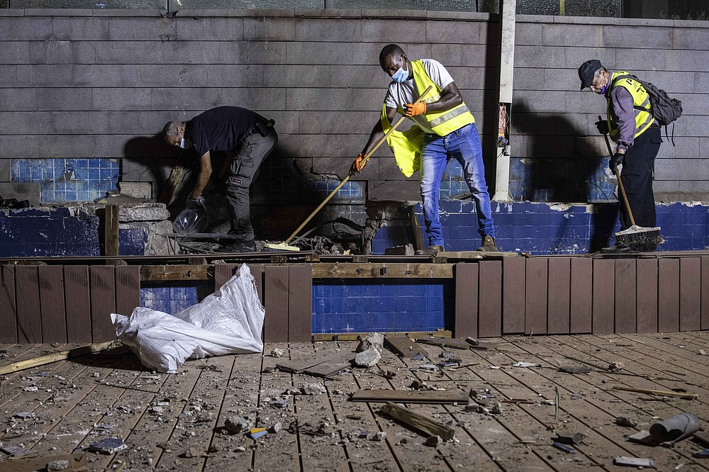Israeli police inspect the damage at the site hit by a rocket fired by Palestinian militants from the Gaza Strip in the southern city of Ashdod, Israel, Tuesday, Sept. 15, 2020. The Israeli military says two rockets were fired from Gaza and one was intercepted by air defenses. Magen David Adom, the Israeli emergency service, says it treated two people for minor injuries from broken glass. (AP Photo/Tsafrir Abayov)