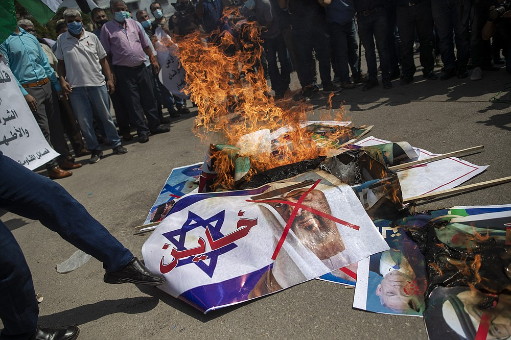 "Palestinians burn pictures of U.S. President Donald Trump, Israeli Prime Minister Benjamin Netanyahu, Bahrain's King Hamad bin Isa Al Khalifa and and Abu Dhabi Crown Prince Mohammed bin Zayed al-Nahyan, during a protest against the United Arab Emirates and Bahraini normalization agreement with Israel, in Gaza City, Tuesday, Sept. 15, 2020. Israel is set to sign agreements with the UAE and Bahrain at the White House on Tuesday. Arabic on poster with representation of an Israeli flag reads, ""traitor."" (AP Photo/Khalil Hamra)"
