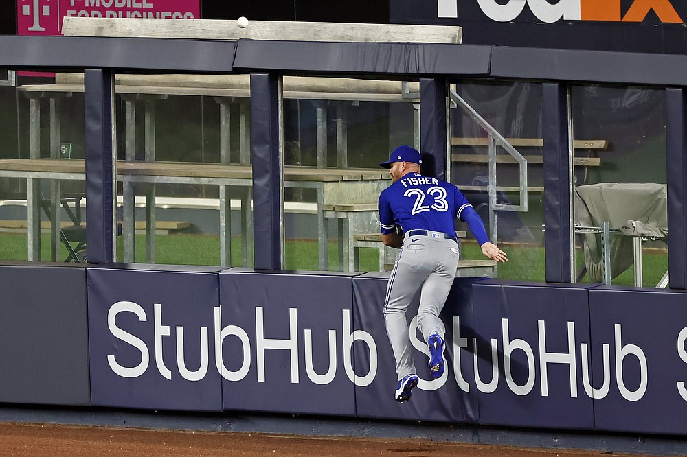 Toronto Blue Jays right fielder Derek Fisher crashes into the wall chasing a single by New York Yankees' Brett Gardner during the second inning of a baseball game Tuesday, Sept. 15, 2020, in New York. (AP Photo/Adam Hunger)