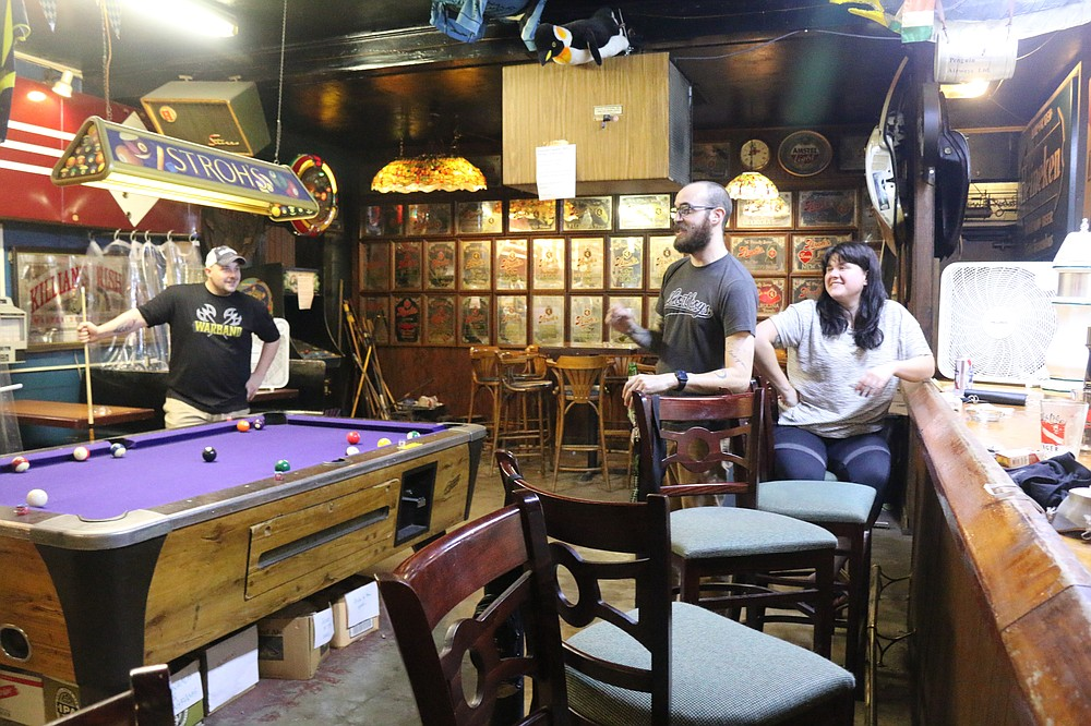 Matt Helms, far left, chats with Zach Preston and his wife Allie Preston at The Leon Pub in Tallahassee, Fla., on Monday night, Sept. 14, 2020. They have been regulars at the once-popular watering hole, which is trying to revive its business in the wake of the coronavirus pandemic. (AP Photo/Bobby Caina Calvan)
