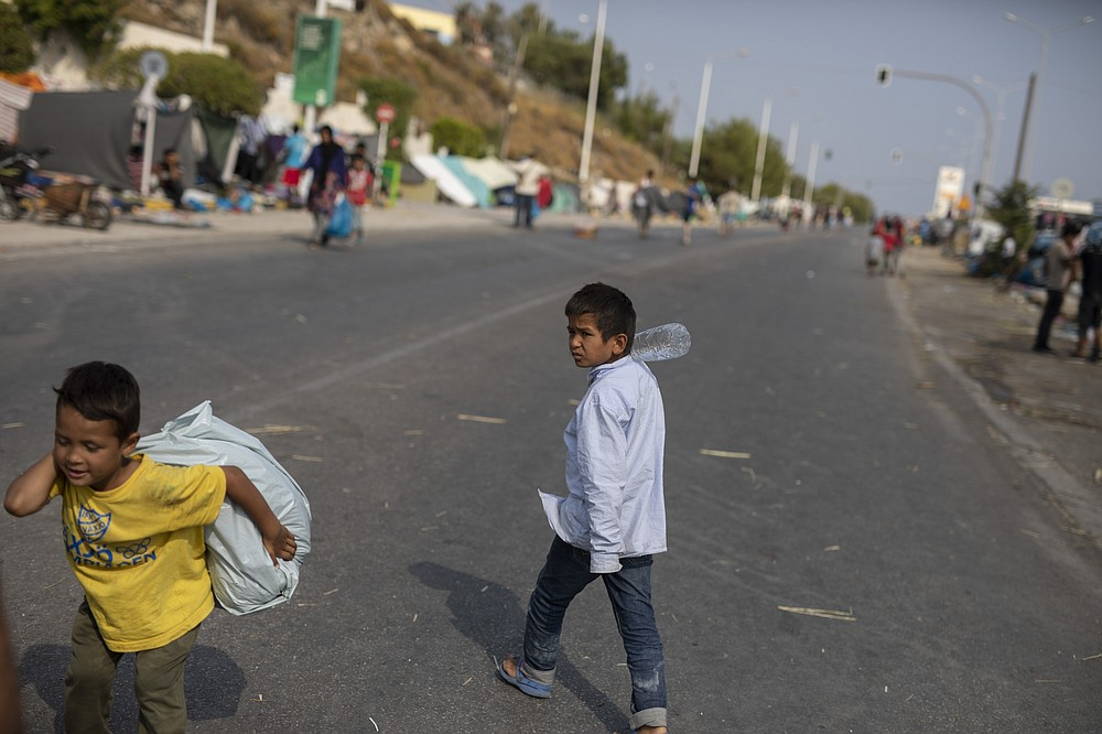 A boy carries a plastic bag as migrants gather on the roadside near Mytilene town, on the northeastern island of Lesbos, Greece, Tuesday, Sept. 15, 2020. Just over 6% of the 12,500 people left homeless last week by the fire that destroyed Greece's biggest camp for refugees and migrants have been rehoused in a new temporary facility under construction on the island of Lesbos. (AP Photo/Petros Giannakouris)