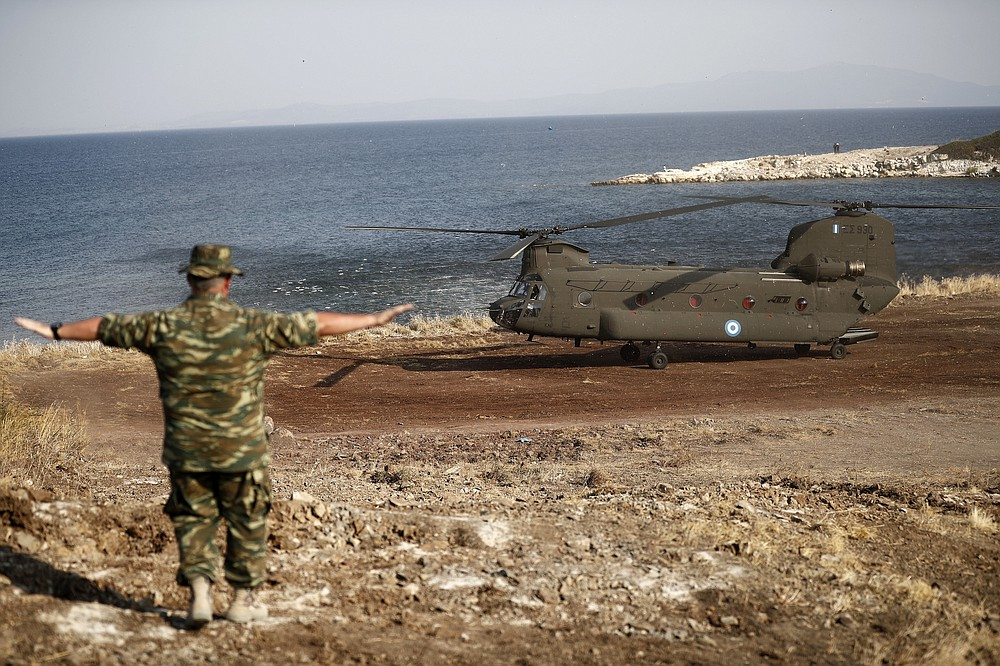A Greek Army helicopter carrying the European Council President Charles Michel lands in the new temporary refugee camp in Kara Tepe on the northeastern island of Lesbos, Greece, Tuesday, Sept. 15, 2020. Greece has called on the European Union to jointly run new refugee camps being built on its eastern islands as part of a planned overhaul of the bloc's migration policy. (Dimitris Tosidis/Pool via AP)