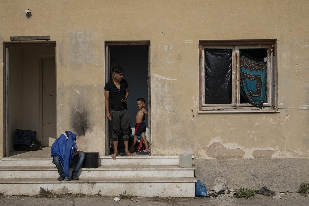 Migrants gather at an abandoned building near Mytilene town, on the northeastern island of Lesbos, Greece, Tuesday, Sept. 15, 2020. Just over 6% of the 12,500 people left homeless last week by the fire that destroyed Greece's biggest camp for refugees and migrants have been rehoused in a new temporary facility under construction on the island of Lesbos. (AP Photo/Petros Giannakouris)