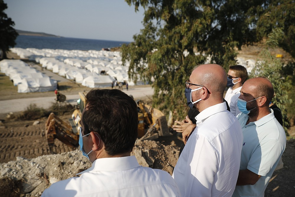 European Council President Charles Michel, center, accompanied by Greek officials, looks at the new temporary refugee camp in Kara Tepe during his visit on the northeastern island of Lesbos, Greece, Tuesday, Sept. 15, 2020. Greece has called on the European Union to jointly run new refugee camps being built on its eastern islands as part of a planned overhaul of the bloc's migration policy. (Dimitris Tosidis/Pool via AP)