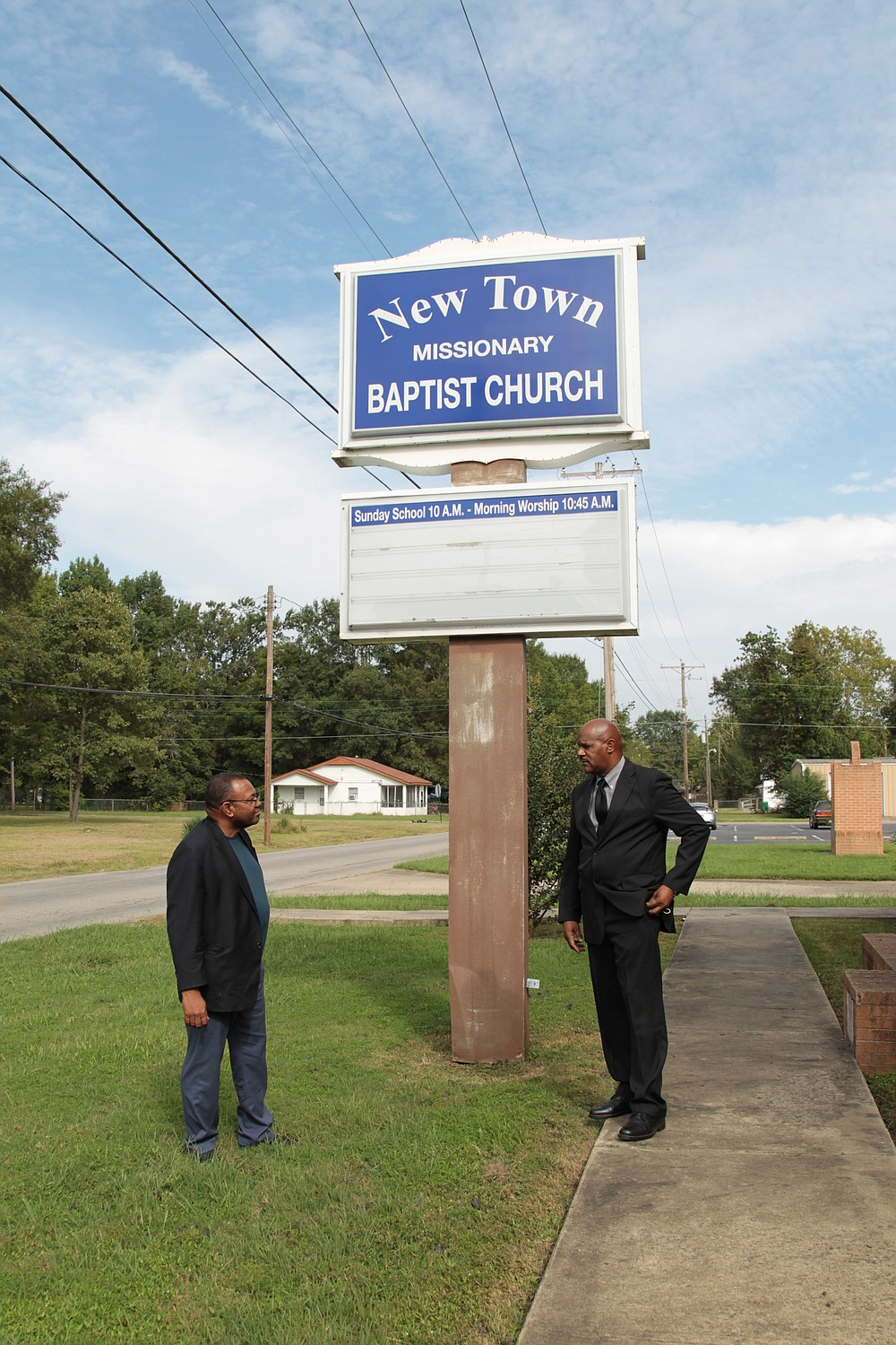 Ward Four aldermen Bruce Lockett, on left, and Steven Mays talk in front of New Town Missionary Baptist Church, which was discontinued as a polling site following a January decision by election commissioners Michael Adam and Stuart Soffer. Lockett and Mays, along with Ward Four resident Walter Johnson, have filed suit in Jefferson County Circuit Court seeking an injunction to allow the site to be used in the upcoming November 3 General Election. (Pine Bluff Commercial/Dale Ellis)