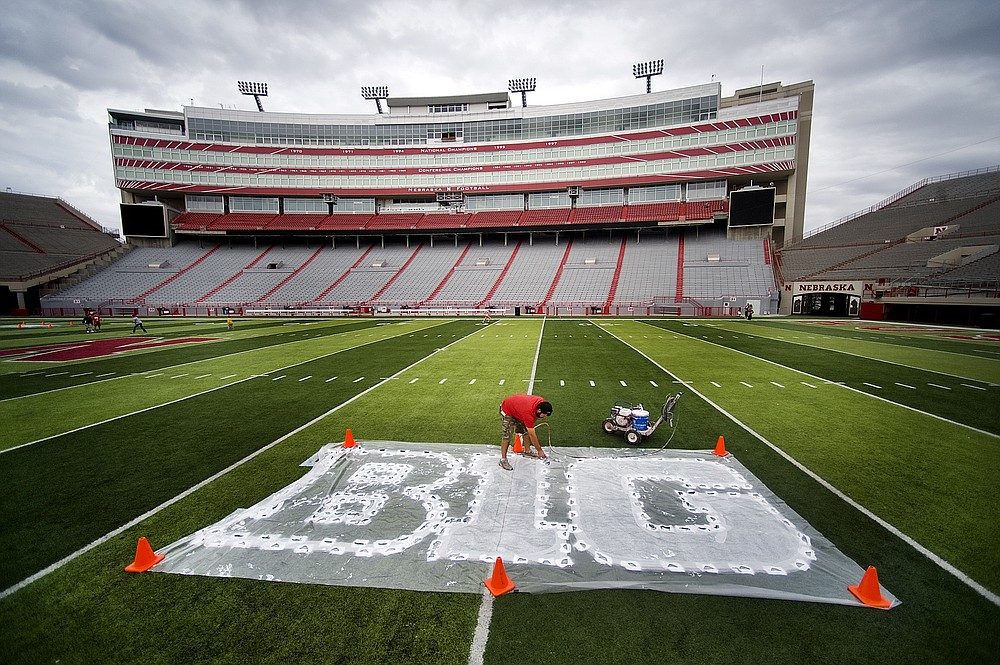 FILE - In this Thursday, Oct. 6, 2011 file photo, turf manager Jared Hertzel touches up the newly-painted Big Ten conference logo on the football field at Memorial Stadium in Lincoln, Neb. Big Ten is going to give fall football a shot after all. Less than five weeks after pushing football and other fall sports to spring in the name of player safety during the pandemic, the conference changed course Wednesday and said it plans to begin its season the weekend of Oct. 23-24. (Jacob Hannah/Lincoln Journal Star via AP, File)