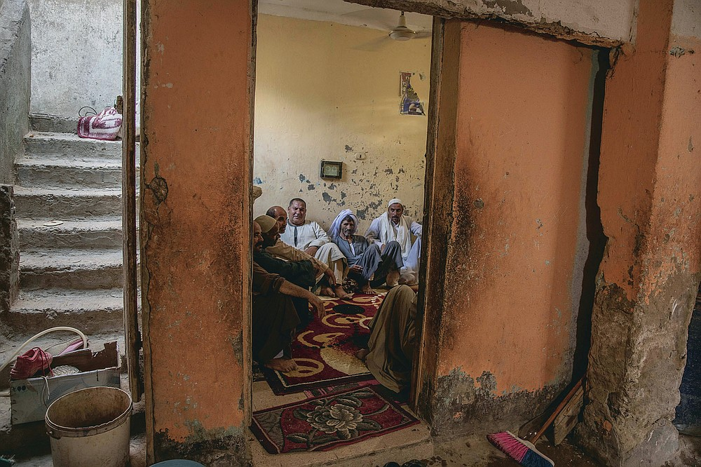 """55-year-old Egyptian farmer Makhluf Abu Kassem, left, sits with farmers in his home, in Second Village, Qouta town, Fayoum, Egypt, Saturday, Aug. 8, 2020. Abu Kassem fears that a dam Ethiopia is building on the Blue Nile, the Nile's main tributary, could add to the severe water shortages already hitting his village if no deal is struck to ensure a continued flow of water. """"The dam means our death,"""" he said. (AP Photo/Nariman El-Mofty)"""
