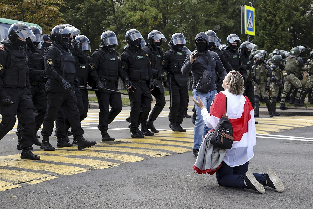 A woman covered herself by an old Belarusian national flag kneels in front of a riot police line as they block Belarusian opposition supporters rally protesting the official presidential election results in Minsk, Belarus, Sunday, Sept. 13, 2020. Protests calling for the Belarusian president's resignation have broken out daily since the Aug. 9 presidential election that officials say handed him a sixth term in office. (TUT.by via AP)