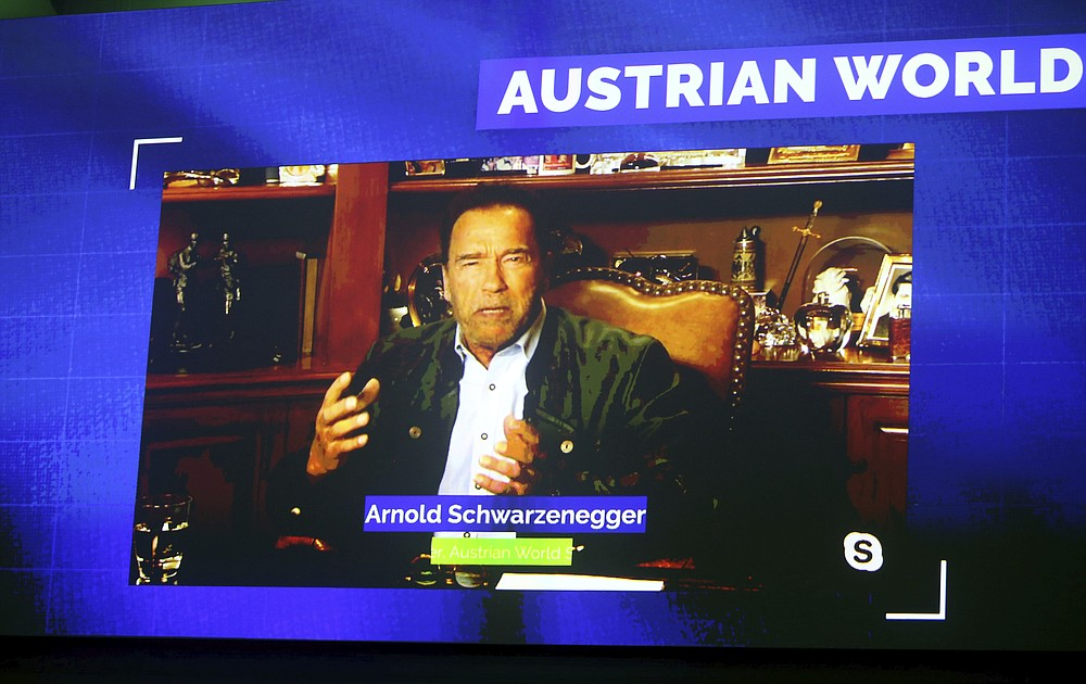 Former California Gov. Arnold Schwarzenegger is seen on a giant video screen during his online broadcasted speech as part of the 'Austrian World Summit' at the Spanish Riding School in Vienna, Austria, Thursday, Sept. 17, 2020. (AP Photo/Ronald Zak)
