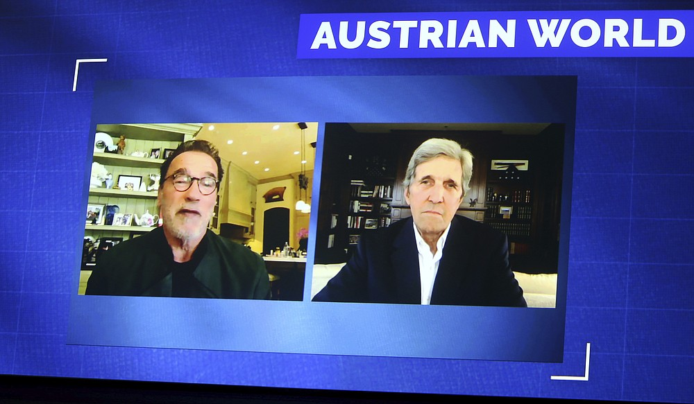 Former California Gov. Arnold Schwarzenegger, left, and Former US Secretary of State John Kerry, right, are seen on a giant video screen during an online broadcasted interview as part of the 'Austrian World Summit' at the Spanish Riding School in Vienna, Austria, Thursday, Sept. 17, 2020. (AP Photo/Ronald Zak)