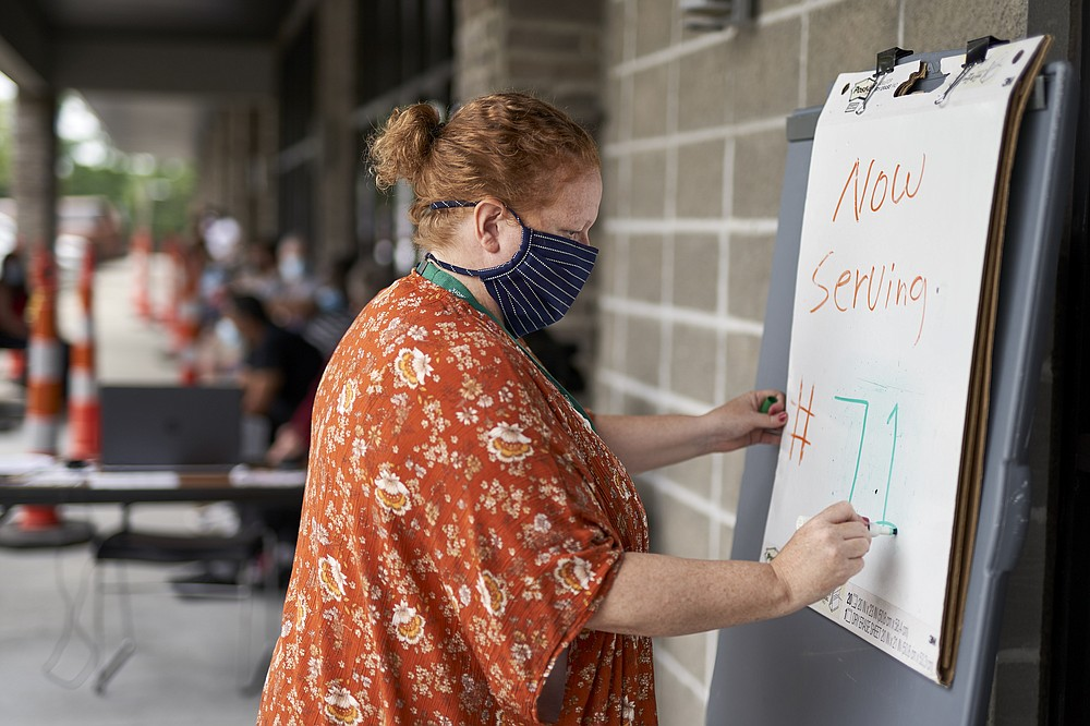 FILE - In this July 15, 2020, file photo, one-stop operator Vickie Gregorio with the Heartland Workforce Solutions updates a whiteboard outside the workforce office in Omaha, Neb., as those seeking employment await their turn outside. The Labor Department reported unemployment numbers Thursday, Sept. 3. (AP Photo/Nati Harnik, File)