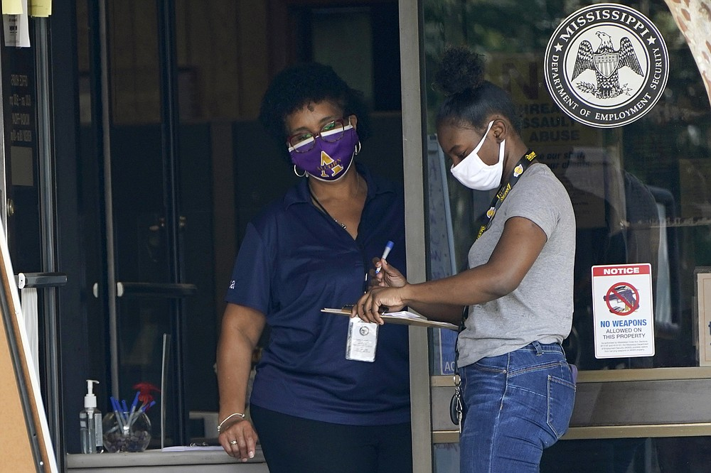 An employee of the Mississippi Department of Employment Security WIN Job Center in Pearl, Miss., left, assists a client fill out paperwork, Monday, Aug. 31, 2020. The Labor Department reported unemployment numbers Thursday, Sept. 3. (AP Photo/Rogelio V. Solis, File)