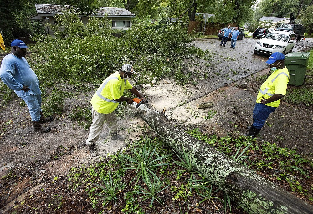 Crews cut up a large downed tree limb, Thursday, Sept. 17, 2020, in Montgomery, Ala. Homeowners and businesses along the soggy Gulf Coast have begun cleaning up in the wake of Hurricane Sally, even as the region braces for a delayed, second round of flooding in the coming days from rivers and creeks swollen by the storm's heavy rains. (Mickey Welsh/The Montgomery Advertiser via AP)