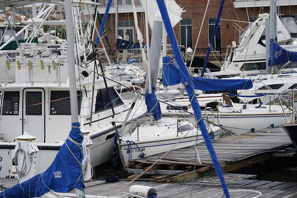 Storm damaged boats sit at the dock in a marina, Thursday, Sept. 17, 2020, in Pensacola, Fla. Rivers swollen by Hurricane Sally's rains threatened more misery for parts of the Florida Panhandle and south Alabama on Thursday, as the storm's remnants continued to dump heavy rains inland that spread the threat of flooding to Georgia and the Carolinas.(AP Photo/Gerald Herbert)