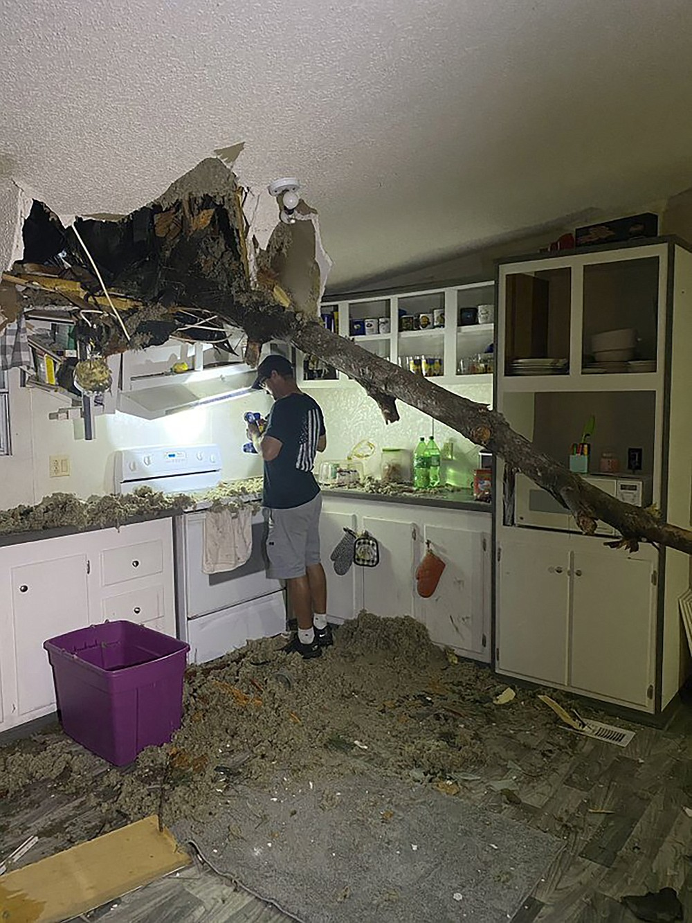 ADDS MAN IN PHOTO IS THE HOMEOWNER - A tree limb juts through the ceiling of a home as the homeowner turns on a flashlight to begin cleaning up the damage left by Hurricane Sally on Thursday, Sept. 17, 2020, in Guyton, Ga.   (WTOC-TV via AP)