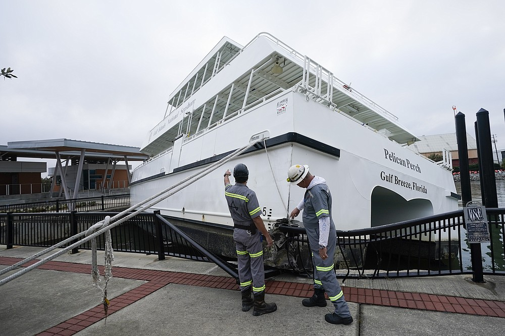 Workers look over a damaged ferry , Thursday, Sept. 17, 2020, in Pensacola, Fla. Rivers swollen by Hurricane Sally's rains threatened more misery for parts of the Florida Panhandle and south Alabama on Thursday, as the storm's remnants continued to dump heavy rains inland that spread the threat of flooding to Georgia and the Carolinas.(AP Photo/Gerald Herbert)