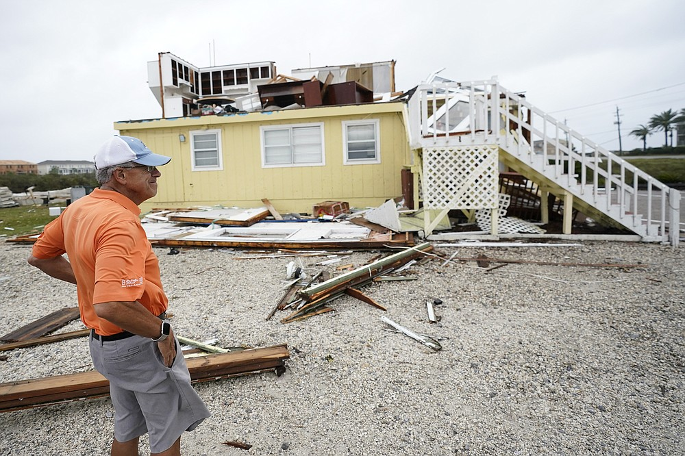 Joe Mirable surveys the damage to his business after Hurricane Sally moved through the area, Wednesday, Sept. 16, 2020, in Perdido Key, Fla. Hurricane Sally made landfall Wednesday near Gulf Shores, Alabama, as a Category 2 storm, pushing a surge of ocean water onto the coast and dumping torrential rain that forecasters said would cause dangerous flooding from the Florida Panhandle to Mississippi and well inland in the days ahead. (AP Photo/Gerald Herbert)