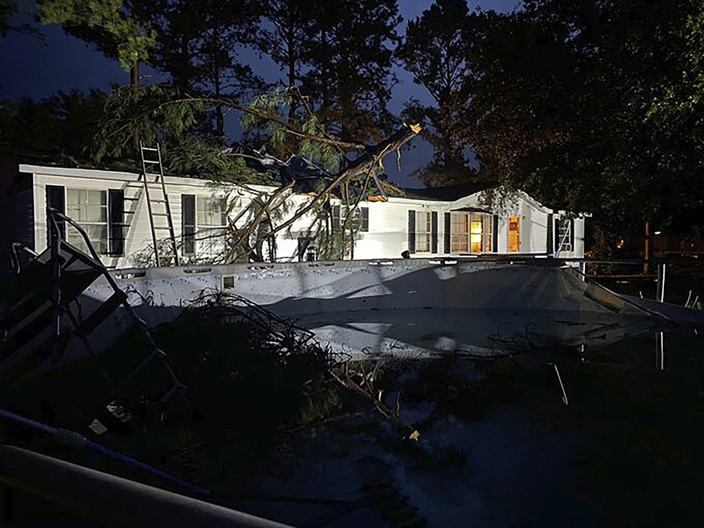 Fallen tree limbs lay on top of a home and above ground pool damaged by Hurricane Sally, which weakened to a tropical depression, on Thursday, Sept. 17, 2020,  in Guyton, Ga.  (WTOC-TV via AP)