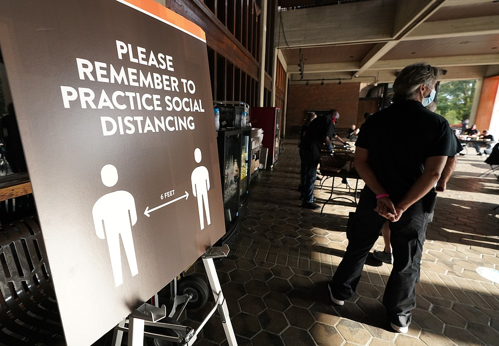 Event staff stand at the entrance to the Grand Ole Opry House stand near signs encouraging social distancing during the 55th annual Academy of Country Music Awards on Wednesday, Sept. 16, 2020, in Nashville, Tenn. (AP Photo/Mark Humphrey)