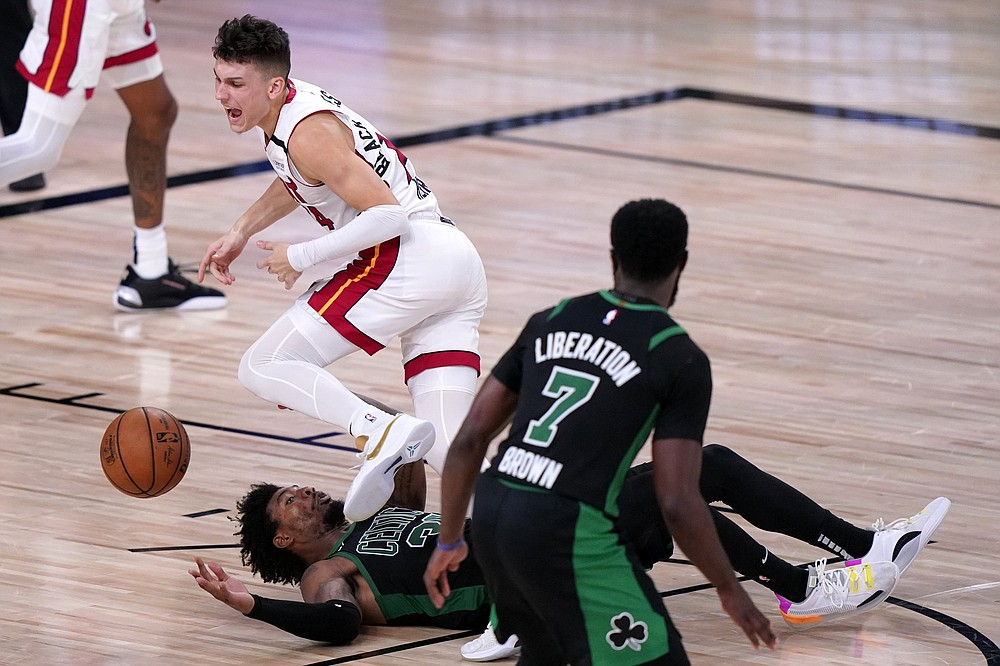 Miami Heat guard Tyler Herro (14) loses control of the ball as he works against Boston Celtics guard Marcus Smart, bottom, and Jaylen Brown (7) during the second half of an NBA conference final playoff basketball game, Thursday, Sept. 17, 2020, in Lake Buena Vista, Fla. (AP Photo/Mark J. Terrill)