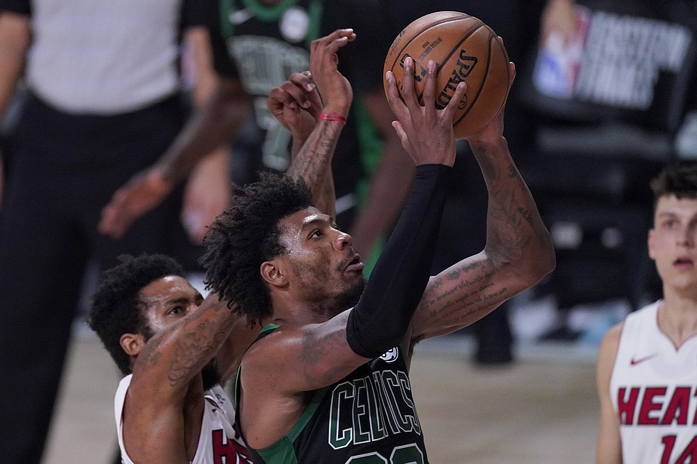 Boston Celtics guard Marcus Smart, front, goes up for a shot as Miami Heat's Derrick Jones Jr., left, and Tyler Herro, right, defend during the second half of an NBA conference final playoff basketball game, Thursday, Sept. 17, 2020, in Lake Buena Vista, Fla. (AP Photo/Mark J. Terrill)